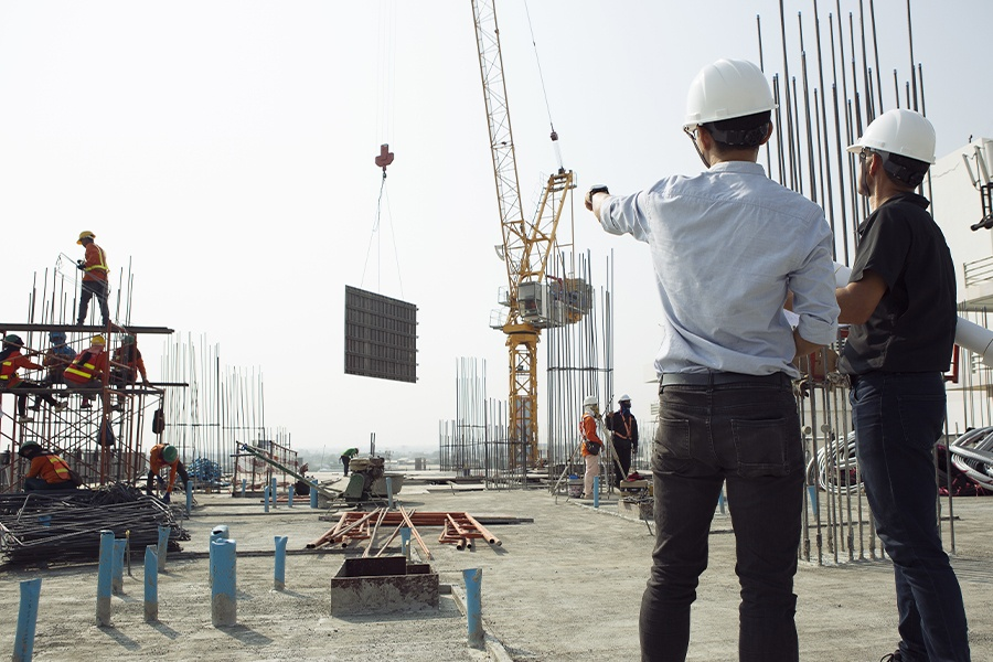 Specialized Business Insurance - Two Engineers Work and Check their Progress on a Construction Site